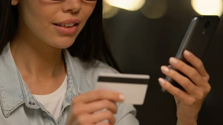 motive : Cheerful lady typing credit card data in mobile application, online shopping