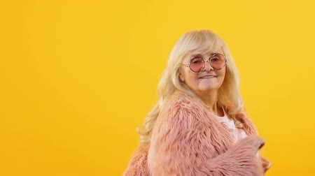 fiatalos : Stylish granny in pink fur and eyeglasses moving to music, dancing party, style Stock mozgókép