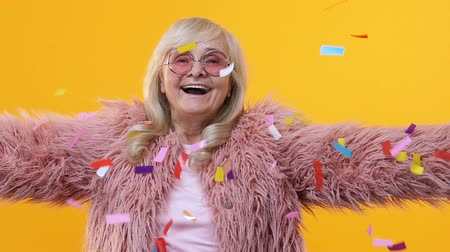 fiatalos : Cheerful senior woman stylish fur enjoying falling confetti, festival happiness