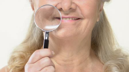 анализ : Aged female holding magnifying glass on wrinkled old face, anti-age cosmetics