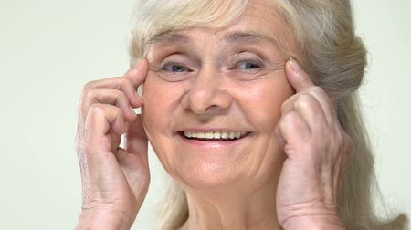 dermatologia : Smiling old woman stretching eye wrinkles up, face contouring anti-aging massage