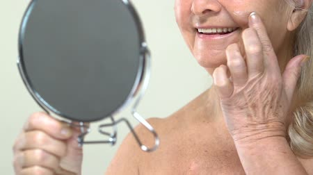 femininity : Old woman applying anti-aging face cream in front of small mirror, body care