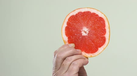 grejpfrut : Female hand holding juicy grapefruit slice, diet and detox, vitamins supplement