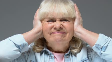 barulhento : Annoyed grandmother covering ears by hands, loud sound stress, feeling headache