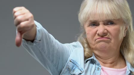 disapprove : Upset grandmother showing thumbs down, negative gesture, disappointment sign