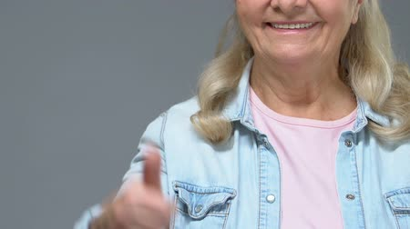 egyetért : Positive grandmother showing thumbs up, good mood, approval gesture satisfaction