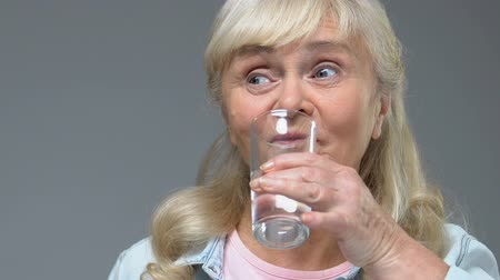 suplementy : Senior woman tasting white vitamin pill and drinking water from glass, treatment Wideo