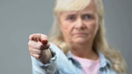 condemn : Angry old woman pointing by finger in camera, condemnation gesture, disapproval