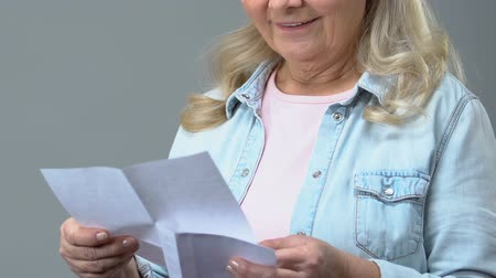 muhabir : Happy grandmother reading letter holding envelope in hand, correspondence, news