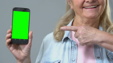 пенсия : Smiling mature female pointing at smartphone in hand, green screen, application