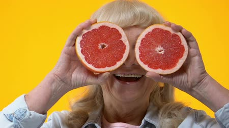 eye piece : Cheerful aged woman holding grapefruit slices front of eyes, fruits nutrition Stock Footage