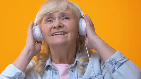 favori : Elderly woman in white headphones listening to music, enjoying favorite melody