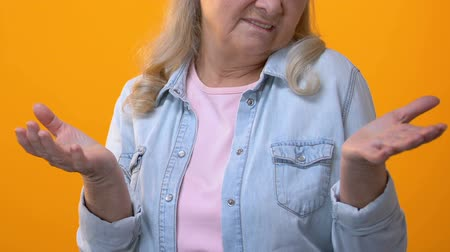 disinterest : Displeased grandmother gesturing hands on yellow background, negative reaction