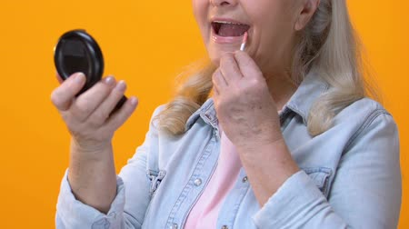 melisa : Senior woman applying lip gloss in front of small mirror, anti-aging cosmetics