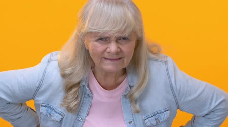 disapprove : Disappointed granny looking angrily on yellow background, old generation, accuse