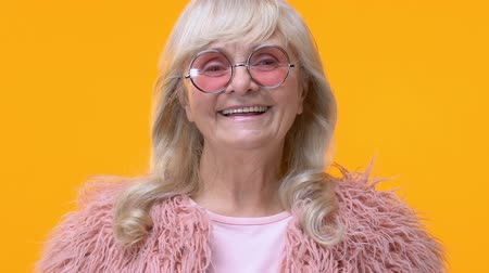 fiatalos : Modern aged woman in pink glasses smiling camera on yellow background, glamour