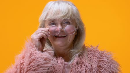 шестидесятые годы : Fashionable old woman taking off pink glasses and smiling in camera, happiness