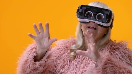 travessura : Funny senior woman in virtual reality goggles yellow background, entertainment