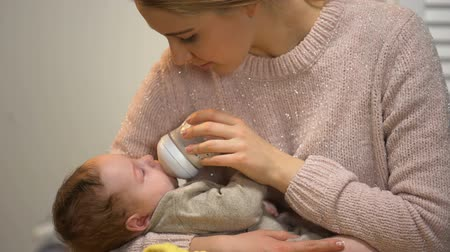 colic : Mommy feeding little cute baby from bottle and talking to him tenderly, care Stock Footage