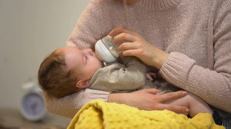 colic : Babysitter feeding cute little child from bottle, artificial feeding accessories