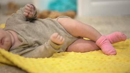 apertado : Charming baby girl lying on yellow blanket, thigh joints dysplasia prevention