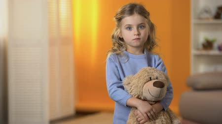 animal adoption : Adorable sad little girl hugging favorite teddy bear feeling lonely in orphanage