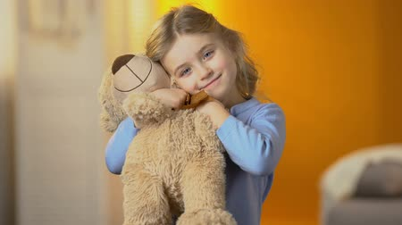 peluş : Cute curly-haired blond girl hugging teddy bear and smiling to camera, happiness