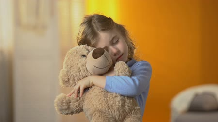 animal adoption : Little lonely girl hugging teddy bear, suffering loneliness, family problems Stock Footage
