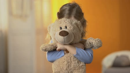 félénk : Preschool shy girl hiding behind teddy bear, childish psychological problems