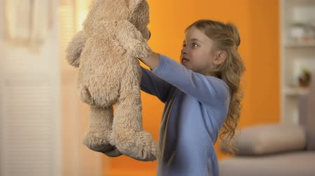 favori : Cute little girl looking at teddy bear and hugging it, favorite toy, childhood Stok Video