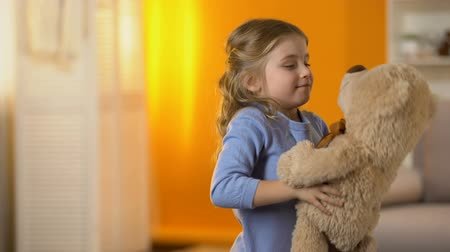 peluş : Happy blond curly-haired little girl playing with favorite teddy bear, childhood Stok Video