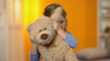 favori : Playful adorable girl hiding behind plush toy and smiling to camera, preschooler