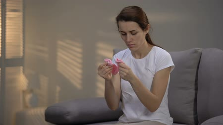 forced : Desperate lady looking at pink socks and pressing them to chest, pregnancy loss