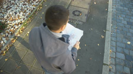 urban exploration : Young man with city map lost on street, tourist searching for destination place Stock Footage