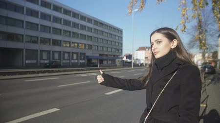 hurry up : Young woman catching taxi on street in morning, late for work, hitchhiking Stock Footage