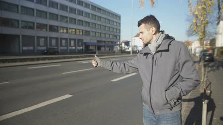 hurry up : Young man catching automobile in unknown city, cheap traveling, hitchhiking Stock Footage