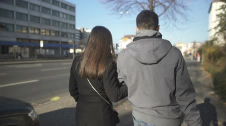 tricky : Young couple walking on street and looking back, swindlers leaving crime place Stock Footage