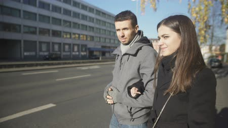 liften : Young couple standing near road, man unconfidently catching taxi.