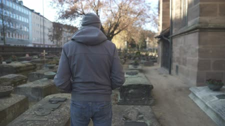 heaven and hell : Young man walking on ancient cemetery between graves, historical place, memory Stock Footage