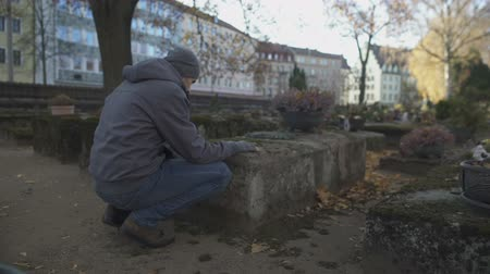 heaven and hell : Young man sitting near grave on ancient cemetery praying, mourning for relatives