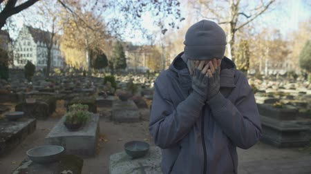 heaven and hell : Man standing on cemetery and deeply crying, missing lost family, loneliness Stock Footage