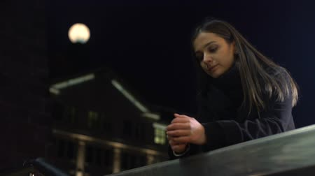 concerned girl : Pensive young woman standing on night city street and thinking about life