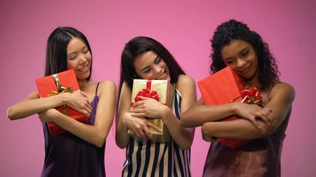 exited : Multiracial women in pajamas holding gift boxes, secret santa party, celebration