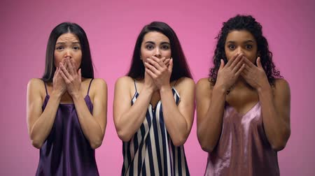 pajama : Shocked girls closing mouth with hands against pink background, gossips news