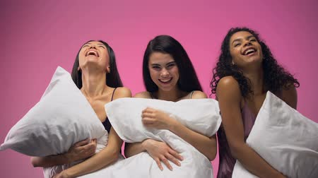 yatak kıyafeti : Adorable women with pillows having fun and laughing out loud, pajamas party Stok Video