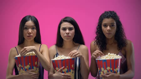 pop corn : Confused women eating popcorn and attentively watching movie, interesting film Vidéos Libres De Droits