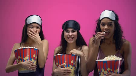 enjoyable : Three girls with eye masks eating popcorn and laughing out loud, funny comedy Stock Footage