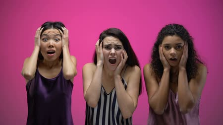 ужасный : Shocked multiracial female friends watching awful tv show, negative emotions