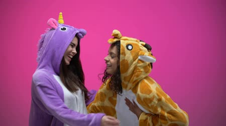 piada : Funny young women wearing unicorn and giraffe pajamas, laughing, entertainment
