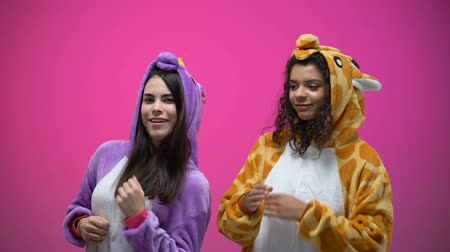 jó hangulatban : Female friends in unicorn and giraffe pajamas dancing, carnival party, fun time Stock mozgókép